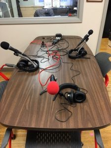 Podcasting table with microphones, H5 recorder, H6 zoom adaptor for 4 mics, headphone splitter, and mic stands.