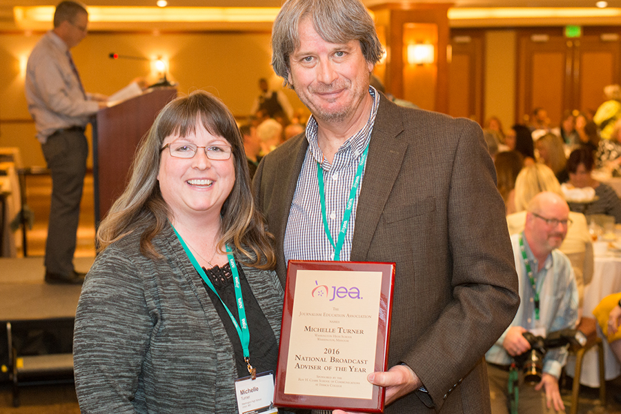 Michelle Tuner receives her 2015 National Broadcast Adviser of the Year plaque from JEA President Mark Newton in Los Angeles.