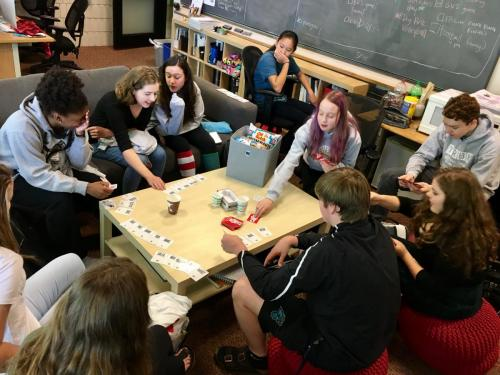 The Ibid yearbook staff plays Heads, You Win (a headline game) and eating snacks. The coffee table is an awesome place for the staff to hang out and bond.